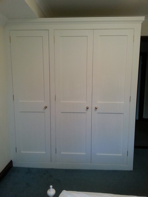 Traditional triple wardrobe in Quendon, Essex. Shaker style doors with no mouldings into panels. V-groove&beaded mdf on side of unit.